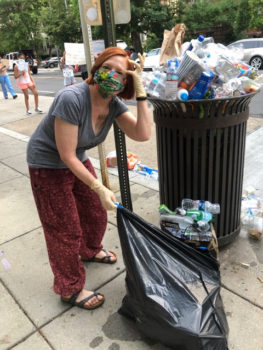 A woman picking up trash during the DC protests of 2020
